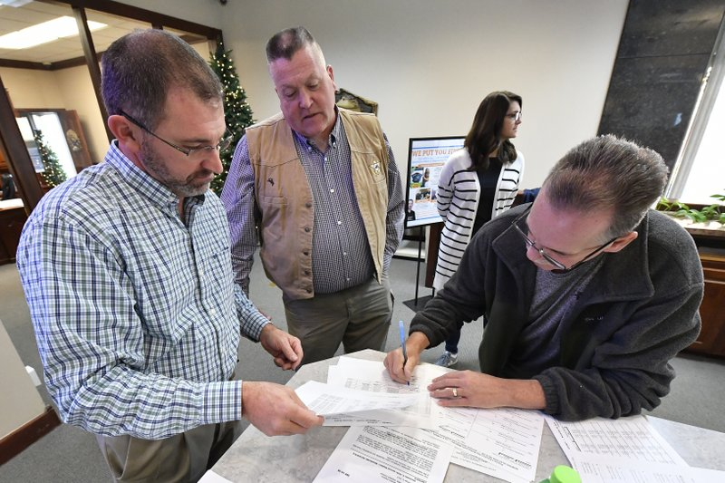 Andrson County Kentucky Board of Elections member Steve Ashburn, right, signs off on the results of the remcanvass of the votes of the election for Kentucky Governor in Lawrenceburg, Ky., Thursday, Nov. 14, 2019. Right is Anderson Co. Clerk Jason Denny, and center is Anderson Co. Sheriff Joe Milam.  Election officials across Kentucky have started double-checking vote totals that show Republican Gov. Matt Bevin trailing Democrat Andy Beshear by more than 5,000 votes. (AP Photo/Timothy D. Easley)