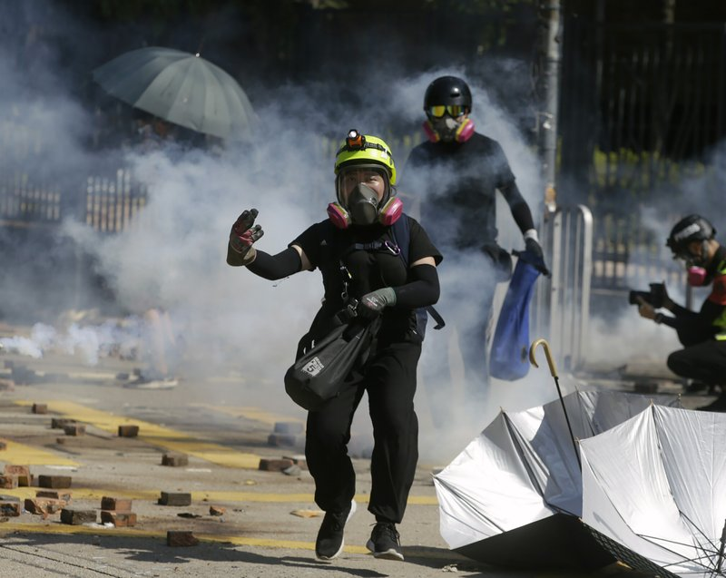 Protestors react as police fire tear gas at Hong Kong Polytechnic University in Hong Kong, Sunday, Nov. 17, 2019. Police fired tear gas Sunday at protesters holding out at Hong Kong Polytechnic University as overnight clashes resumed in the morning. (AP Photo/Achmad Ibrahim)