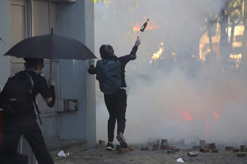A protestor hurls a molotov cocktail during a confrontation with police at the Hong Kong Polytechnic University in Hong Kong, Sunday, Nov. 17, 2019. Police have fired tear gas at protesters holding out at the Hong Kong Polytechnic University as overnight clashes resumed in the morning. (AP Photo/Kin Cheung)