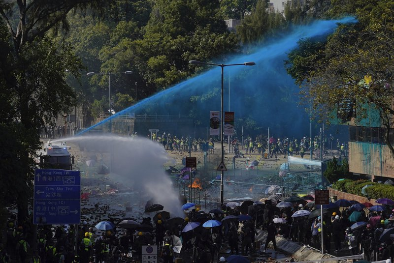 Police spray blue-dyed liquid from an armored vehicle during a confrontation with protestors at the Hong Kong Polytechnic University in Hong Kong, Sunday, Nov. 17, 2019. Police fired tear gas and water canons at protesters holding out at the Hong Kong Polytechnic University as overnight clashes resumed Sunday, and opposition lawmakers criticized the Chinese military for joining a cleanup to remove debris from streets. (AP Photo/Vincent Yu)