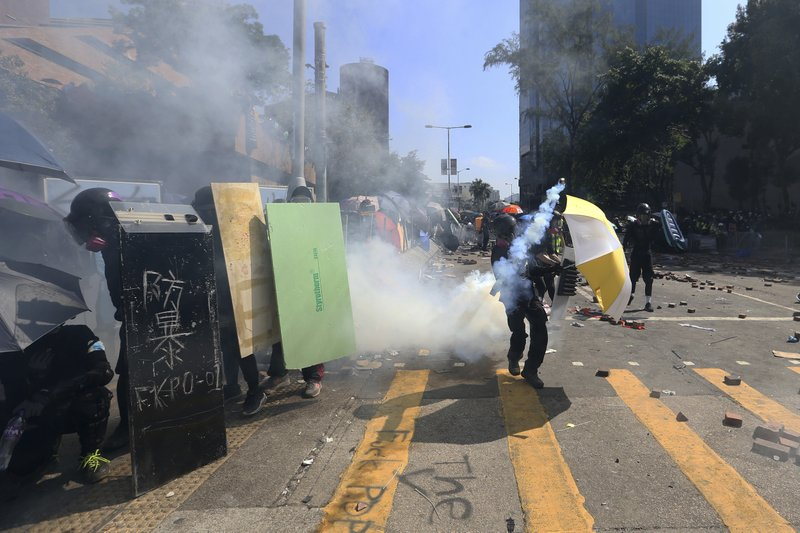 Protestors react during a confrontation with police at the Hong Kong Polytechnic University in Hong Kong, Sunday, Nov. 17, 2019. Police fired tear gas at protesters holding out at the Hong Kong Polytechnic University as overnight clashes resumed Sunday, and opposition lawmakers criticized the Chinese military for joining a cleanup to remove debris from streets. (AP Photo/Achmad Ibrahim)