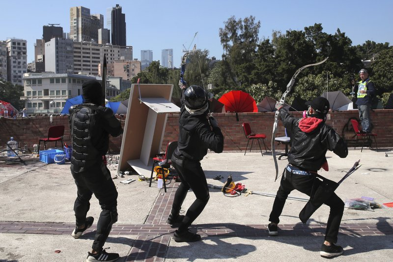 Protestors prepare to shoot bows and arrows during a confrontation with police at Hong Kong Polytechnic University in Hong Kong, Sunday, Nov. 17, 2019. Police fired tear gas at protesters holding out at Hong Kong Polytechnic University as overnight clashes resumed Sunday, and opposition lawmakers criticized the Chinese military for joining a cleanup to remove debris from streets. (AP Photo/Kin Cheung)