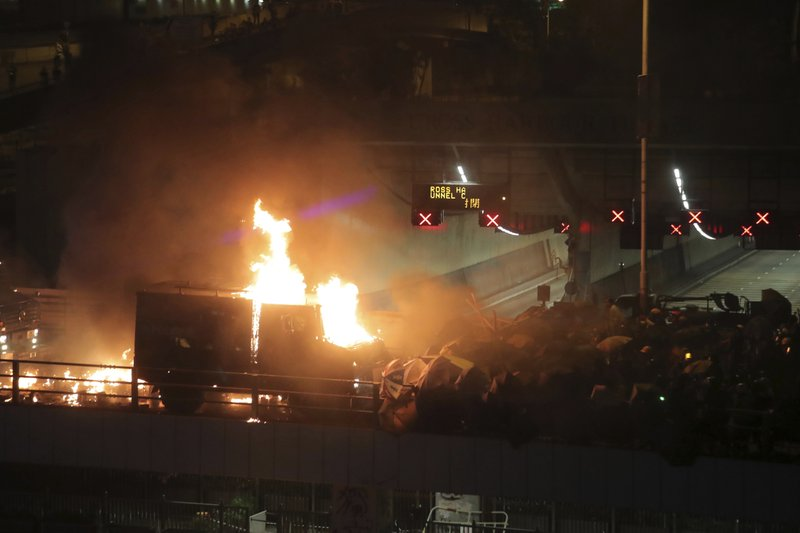 An armored police vehicle catches fire after being hit by molotov cocktails thrown by protestors, at right, on a bridge over a highway leading to the Cross Harbour Tunnel in Hong Kong, Sunday, Nov. 17, 2019. A Hong Kong police officer was hit in the leg by an arrow Sunday as authorities used tear gas and water cannons to try to drive back protesters occupying a university campus and blocking a major road tunnel under the city's harbor. (AP Photo/Kin Cheung)