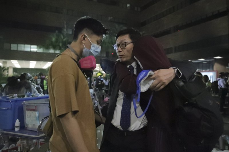 The principal, center, hugs his students at Hong Kong Polytechnic University campus in Hung Hom district, Hong Kong, Monday, Nov. 18, 2019. As night fell in Hong Kong, police tightened a siege Monday at a university campus as hundreds of anti-government protesters trapped inside sought to escape. (AP Photo/Kin Cheung)