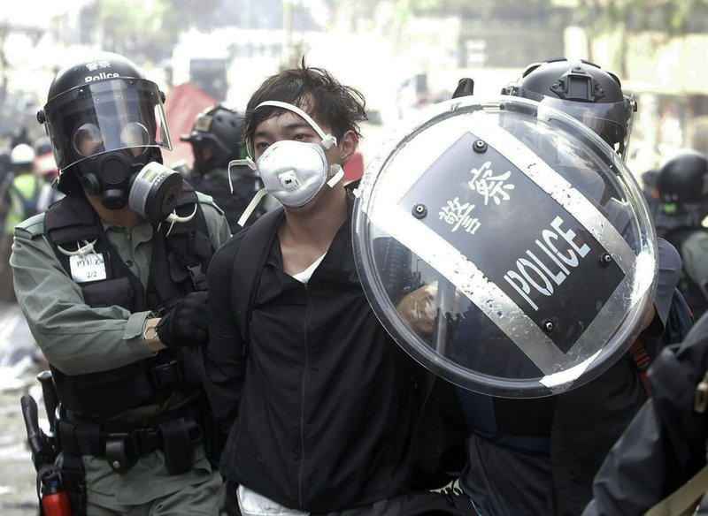 Police officers detain a protester near the Hong Kong Polytechnic University in Hong Kong, Monday, Nov. 18, 2019. Hong Kong police have swooped in with tear gas and batons as protesters who have taken over a university campus make an apparent last-ditch effort to escape arrest. (AP Photo/Achmad Ibrahim)