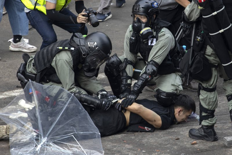 Police detain a protester at the Hong Kong Polytechnic University in Hong Kong, on Nov. 18, 2019. Hong Kong police fought off protesters with tear gas and batons Monday as they tried to break through a police cordon that is trapping hundreds of them on a university campus. (AP Photo/Ng Han Guan)