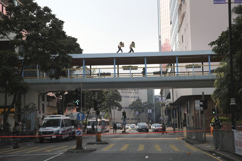 Protesters run across the roof of a pedestrian bridge as they try to escape the Hong Kong Polytechnic University campus in Hong Kong, Monday, Nov. 18, 2019. Hong Kong police using tear gas and rubber bullets fought off protesters Monday as they tried to break through a police cordon that is trapping hundreds of them on a university campus. (AP Photo/Kin Cheung)