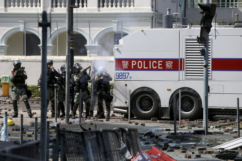 Policemen in riot gear fire teargas outside Hong Kong Polytechnic University in Hong Kong, Monday, Nov. 18, 2019. Hong Kong police have swooped in with tear gas and batons as protesters who have taken over the university campus make an apparent last-ditch effort to escape arrest. (AP Photo/Achmad Ibrahim)