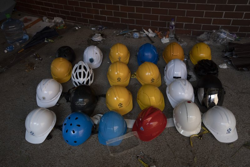 Helmets used by protesters are lined up at the Polytechnic University in Hong Kong on Wednesday, Nov. 20, 2019. A small group of protesters refused to leave Hong Kong Polytechnic University, the remnants of hundreds who took over the campus for several days. They won't leave because they would face arrest. Police have set up a cordon around the area to prevent anyone from escaping. (AP Photo/Ng Han Guan)