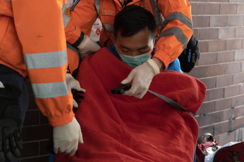 A man is evacuated by medics from the Polytechnic University in Hong Kong on Wednesday, Nov. 20, 2019. Hong Kong schools have reopened after a six-day shutdown but students were facing transit disruptions as the last protesters remained holed up on a university campus. (AP Photo/Ng Han Guan)