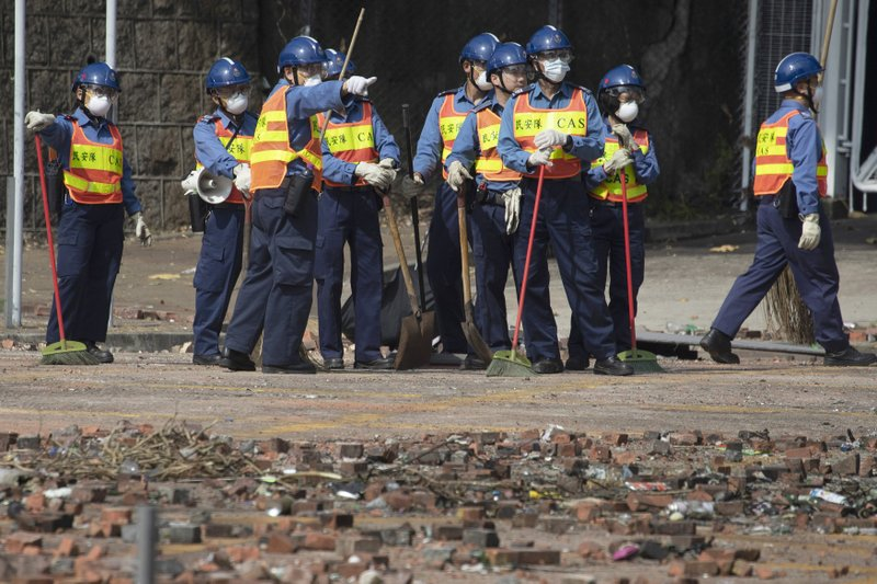 Workers start to clean up the road outside the Hong Kong Polytechnic University in Hong Kong on Wednesday, Nov. 20, 2019. Hong Kong schools have reopened after a six-day shutdown but students were facing transit disruptions as the last protesters remained holed up on a university campus. (AP Photo/Ng Han Guan)