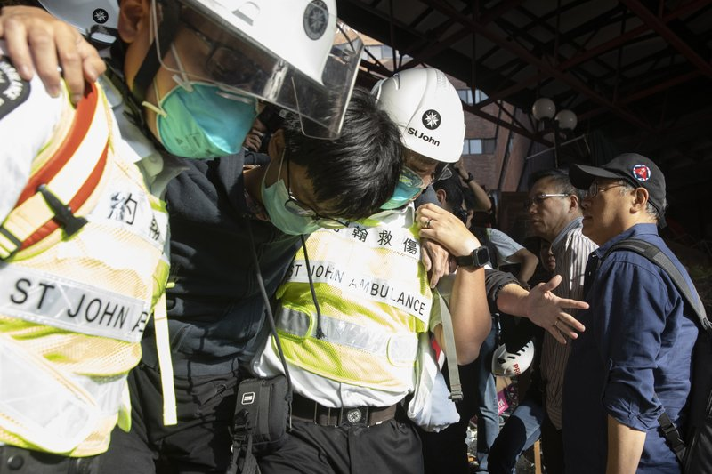 President of the Hong Kong Polytechnic University Jin-Guang Teng, second from right, looks as an injured protester is helped to leave by medics at the University in Hong Kong on Wednesday, Nov. 20, 2019. A small group of protesters refused to leave Hong Kong Polytechnic University, the remnants of hundreds who took over the campus for several days. They won't leave because they would face arrest. Police have set up a cordon around the area to prevent anyone from escaping. (AP Photo/Ng Han Guan)