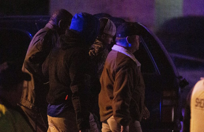The suspect, with the dark and white backwards ball cap, center rear, accused of shooting Lowndes County Sheriff John Williams is surrounded by law enforcement as he walks back to the scene with a firearm, early Sunday, Nov. 24, 2019, in Hayneville, Ala. The suspect was identified as 18-year-old William Chase Johnson. (Kirsten Fiscus/Montgomery Advertiser via AP)