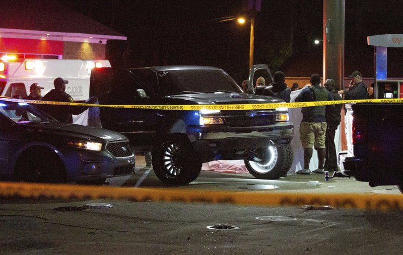 Deputies, police, and state law enforcement work the scene of a QV gas station in Hayneville, Ala., where Lowndes County Sheriff John Williams was shot and killed, Saturday, Nov. 23, 2019. The suspect taken into custody was identified as 18-year-old William Chase Johnson. (Kirsten Fiscus/Montgomery Advertiser via AP)