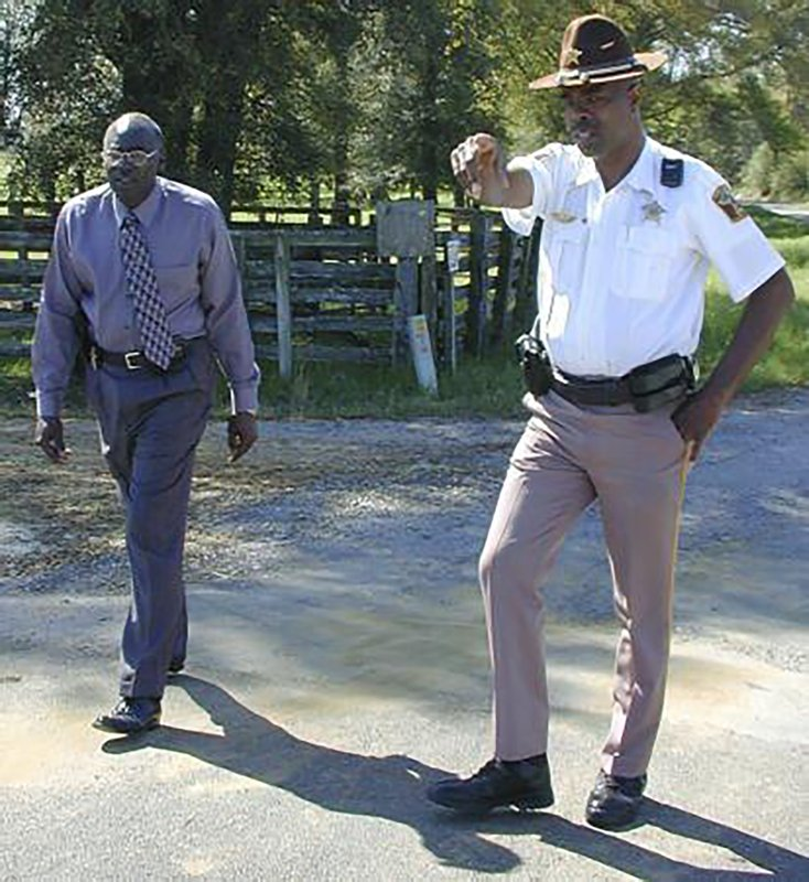 "In this March 21, 2000 photo, Lowndes County Sheriff Willie Vaughner, left, and chief deputy John Williams stand at the intersection where Williams apprehended Jamil Abdullah Al-Amin on Monday evening in White Hall, Ala. Williams was fatally shot in the line of duty Saturday evening, Nov. 23, 2019, in a county near the state capital city, Alabama Gov. Kay Ivey said. Ivey tweeted that Lowndes County Sheriff Williams was ""a pillar of the community.""  (Al Benn/Montgomery Advertiser via AP)"