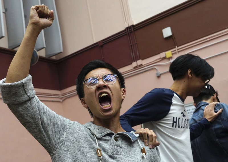 Supporters of a pro-democracy candidate cheer after winning their seat in district council elections in Hong Kong, early Monday, Nov. 25, 2019. Voters in Hong Kong turned out in droves on Sunday in district council elections seen as a barometer of public support for pro-democracy protests that have rocked the semi-autonomous Chinese territory for more than five months. (AP Photo/Vincent Yu)