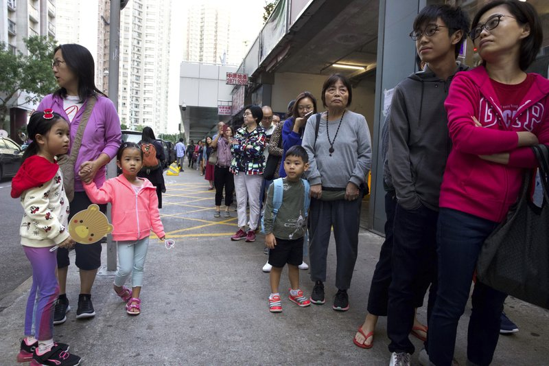 People line up to vote outside of a polling place in Hong Kong, Sunday, Nov. 24, 2019. Voting was underway Sunday in Hong Kong elections that have become a barometer of public support for anti-government protests now in their sixth month. (AP Photo/Ng Han Guan)