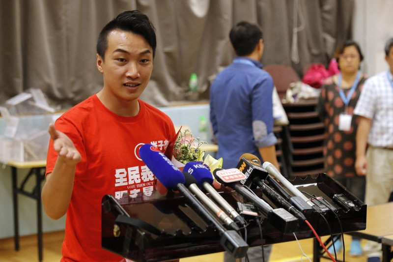 Pro-democracy candidate Jimmy Sham, left, speaks to reporters after winning his election in Hong Kong, early Monday, Nov. 25, 2019. Vote counting was underway in Hong Kong on Sunday after a massive turnout in district council elections seen as a barometer of public support for pro-democracy protests that have rocked the semi-autonomous Chinese territory for more than five months. (AP Photo/Vincent Thian)