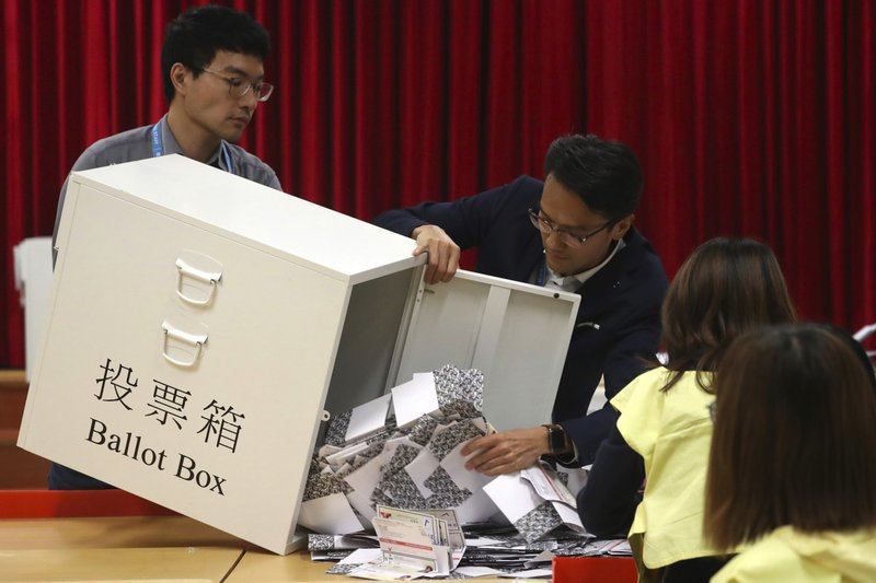 Election workers empty a ballot box to count votes at a polling station in Hong Kong, Sunday, Nov. 24, 2019. Voters in Hong Kong turned out in droves on Sunday in district council elections seen as a barometer of public support for pro-democracy protests that have rocked the semi-autonomous Chinese territory for more than five months. (AP Photo/Ng Han Guan)