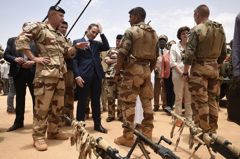 FILE - In this May 19, 2017 file photo, French President Emmanuel Macron, center left, visits soldiers of Operation Barkhane, France's largest overseas military operation, in Gao, Northern Mali. French President Emmanuel Macron said Tuesday Nov.26, 2019 a midair collision between two helicopters has killed 13 French soldiers fighting against Islamic extremists in Mali. (Christophe Petit Tesson, Pool via AP)