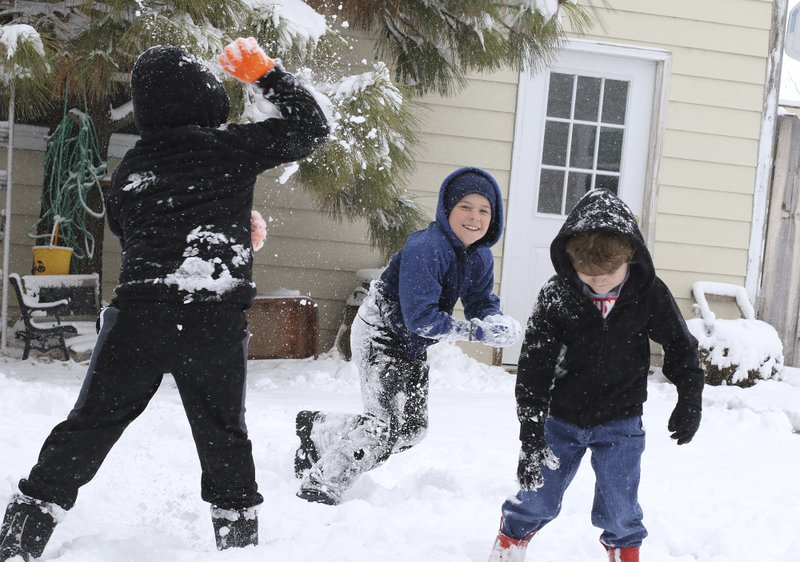 Tuesday's snow called for a snowball fight for the three McKean boys as David, takes aim at his older brother, Ethan Tuesday, Nov. 26, 2019. Younger brother Josiah (5) tried to stay out of the line of fire as the battle raged around him at their home in Scottsbluff, Neb. (Brad Staman/The Star-Herald via AP)