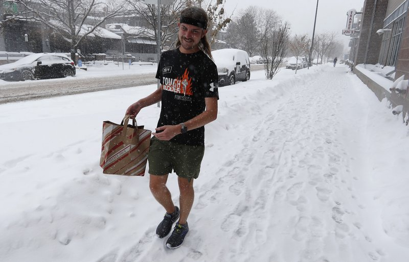 Ryan Lusk, a native of Duluth, Miin., who nows lives in Denver, heads out of a grocery store with his purchases as a storm packing snow and high winds sweeps in over the region Tuesday, Nov. 26, 2019, in Denver. Stores, schools and government offices were closed or curtailed their hours while on another front, Thanksgiving Day travellers were forced to wrestle with snow-packed roads and flight delays or cancellations throughout the intermountain West. (AP Photo/David Zalubowski)