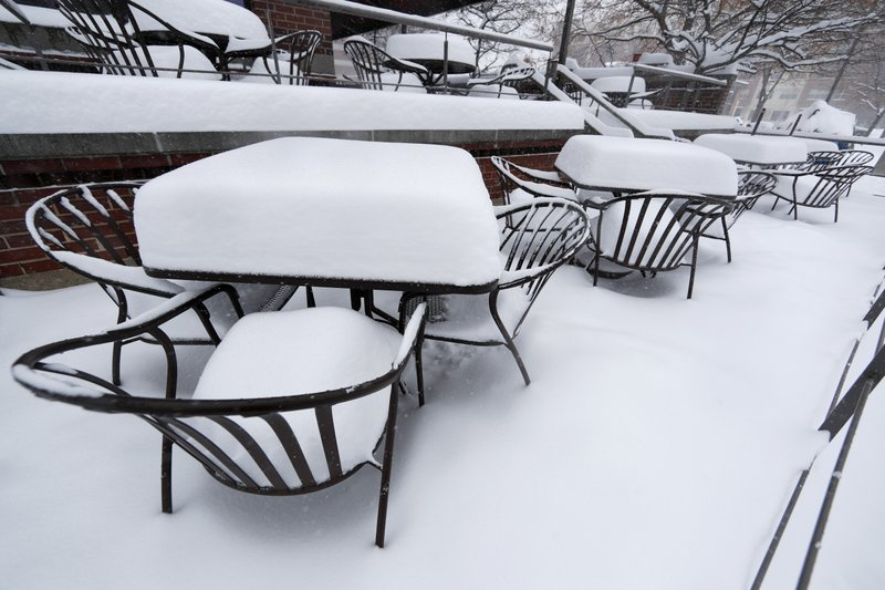 Snow stacks up on the tables on the outside patio of a restaurant as a storm packing snow and high winds sweeps in over the region Tuesday, Nov. 26, 2019, in Denver. Stores, schools and government offices were closed or curtailed their hours while on another front, Thanksgiving Day travellers were forced to wrestle with snow-packed roads and flight delays or cancellations throughout the intermountain West. (AP Photo/David Zalubowski)