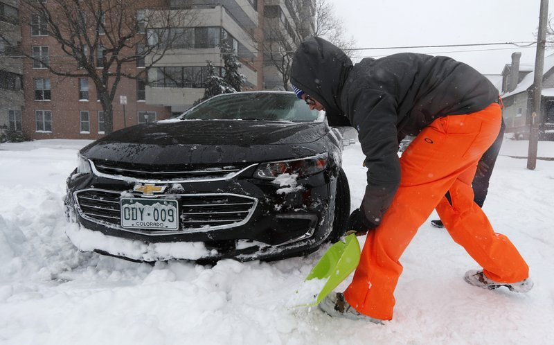 Erik Randa helps dig out a stuck Chevrolet Malibu being used by a ride-sharing service driver out of an intersection at 2nd Ave. and Pearl St. as a storm packing snow and high winds sweeps in over the region Tuesday, Nov. 26, 2019, in Denver. Stores, schools and government offices were closed or curtailed their hours while on another front, Thanksgiving Day travellers were forced to wrestle with snow-packed roads and flight delays or cancellations throughout the intermountain West. (AP Photo/David Zalubowski)