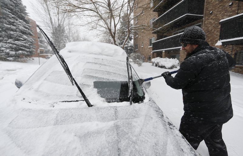 Szymon Lobocki, a rocket engineer from Denver, clears off his Subaru to drive to work in a south suburb as a storm packing snow and high winds sweeps in over the region Tuesday, Nov. 26, 2019, in Denver. Stores, schools and government offices were closed or curtailed their hours while on another front, Thanksgiving Day travelers were forced to wrestle with snow-packed roads and flight delays or cancellations throughout the intermountain West. (AP Photo/David Zalubowski)