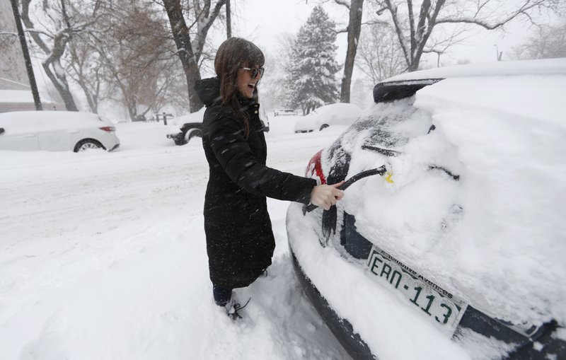 Carli Webber of Denver clears off her sports-utility vehicle to head to work as a storm packing snow and high winds sweeps in over the region Tuesday, Nov. 26, 2019, in Denver. Stores, schools and government offices were closed or curtailed their hours while on another front, Thanksgiving Day travellers were forced to wrestle with snow-packed roads and flight delays or cancellations throughout the intermountain West. (AP Photo/David Zalubowski)