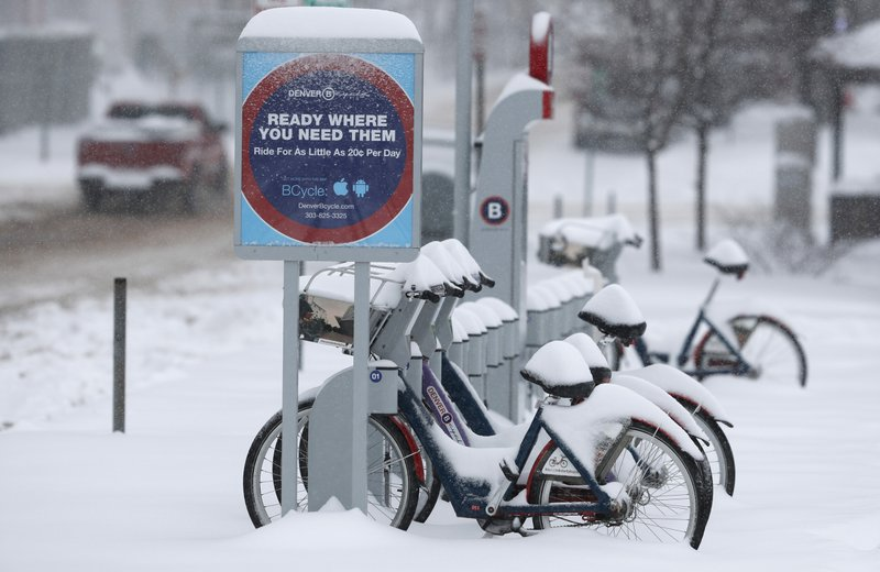 Bicycles used in the city of Denver's Bicycle sharing program are covered in snow as a storm packing snow and high winds sweeps in over the region Tuesday, Nov. 26, 2019, in Denver. Stores, schools and government offices were closed or curtailed their hours while on another front, Thanksgiving Day travellers were forced to wrestle with snow-packed roads and flight delays or cancellations throughout the intermountain West. (AP Photo/David Zalubowski)