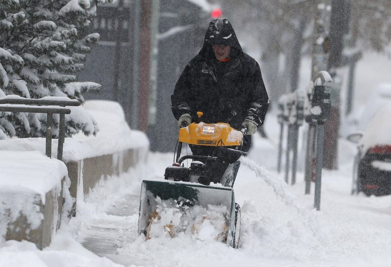 A maintenance man uses a snowblower to clear a sidewalk along 8th Ave. near Lincoln St. as a storm packing snow and high winds sweeps in over the region Tuesday, Nov. 26, 2019, in Denver. Stores, schools and government offices were closed or curtailed their hours while on another front, Thanksgiving Day travellers were forced to wrestle with snow-packed roads and flight delays or cancellations throughout the intermountain West. (AP Photo/David Zalubowski)