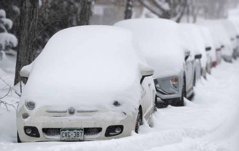 A long line of parked vehicles sits covered with snow as a snowstorm sweeps in over the region Tuesday, Nov. 26, 2019, in Denver. Stores, schools and government offices were closed or curtailed their hours while on another front, Thanksgiving Day travellers were forced to wrestle with snow-packed roads and flight delays or cancellations throughout the intermountain West. (AP Photo/David Zalubowski)