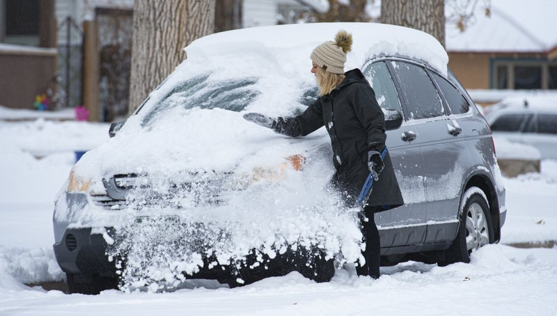 Hanne Murray clears the snow off her car before heading to work Tuesday morning, Nov. 26, 2019, in the Patty Jewett neighborhood of Colorado Springs, Colo. Downtown Colorado Springs reported about six inches of snow overnight will parts of El Paso County tallied more than a foot of snow from the storm. (Christian Murdock/The Gazette via AP)