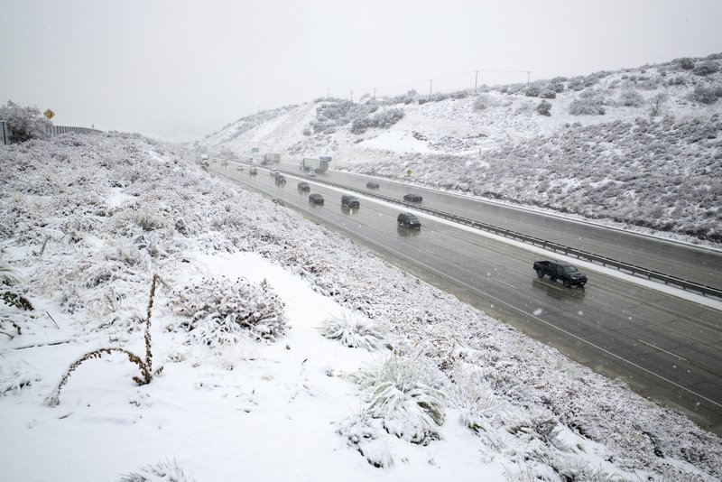 Snow falls along the Interstate 5 freeway at the Tejon Pass as travelers try to get in and out of Southern California for the Thanksgiving holiday, Wednesday, Nov. 27, 2019, near Gorman, Calif.. Plows were running and CHP was guiding traffic in an attempt to keep the freeway open as long as possible.(David Crane/The Orange County Register via AP)