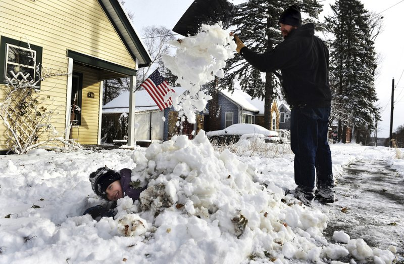 Tim Kalik shovels snow onto his daughter, Lucy, 9, in Stillwater, Minn. on Wednesday morning, Nov. 27, 2019. Lucy has a snow day from school today and is waiting for her friends to go sledding. Tim said he drove into St. Paul to his workplace but they let employees go home around 8:30 due to the weather. (Jean Pieri/Pioneer Press via AP)