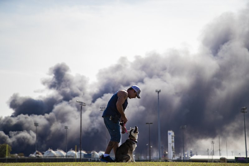 Ray Moore trains his dog Aries with a cloud of smoke in the background from the TPC Group Port Neches Operations explosion on Wednesday, Nov. 27, 2019, in Port Neches, Texas. Multiple workers were injured early Wednesday in a massive explosion at a Texas chemical plant that also blew out the windows and doors of nearby homes. (Marie D. De Jesús/Houston Chronicle via AP)