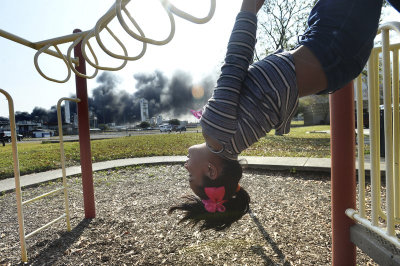 Adanli Puente watches the thick smoke and flames that continued to erupt from the TPC plant as she plays at a nearby park with sister Jullissa Wednesday, November 27, 2019 in Port Neches, Texas. Their father Abraham says the Beaumont family came down to Port Neches to pay their rent and stopped at the park to take photographs of the ongoing fire. (Kim Brent/The Beaumont Enterprise via AP)
