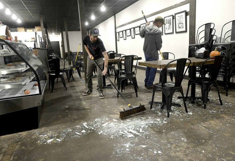 From left, Robert and David Pool sweep up the glass filling the floor and tabletops at The Avenue Coffee Shop after the business' front windows shattered following an explosion at the TPC plant  Wednesday, Nov. 27, 2019, in Port Neches, Texas.  Three workers were injured early Wednesday in a massive explosion at the Texas chemical plant that also blew out the windows and doors of nearby homes.    (Kim Brent