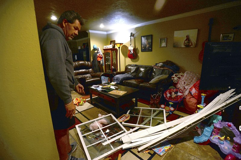 Roger Wallace looks over the damage to his residence after the front window blew out following an explosion at the TPC plant Wednesday, Nov. 27, 2019, in Port Neches, Texas.  Three workers were injured early Wednesday in a massive explosion at the Texas chemical plant that also blew out the windows and doors of nearby homes.    (Kim Brent/The Beaumont Enterprise via AP)