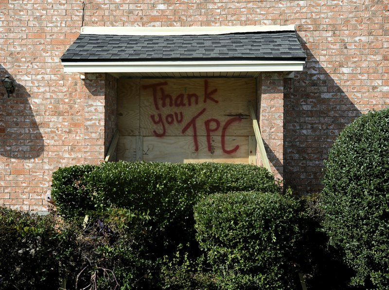 A boarded up window bears a message for TPC Group as residents and business owners throughout Port Neches, Texas clean up from the damage caused by an explosion Wednesday, Nov. 27, 2019    Three workers were injured early Wednesday in a massive explosion at the Texas chemical plant that also blew out the windows and doors of nearby homes.  (Kim Brent/The Beaumont Enterprise via AP)