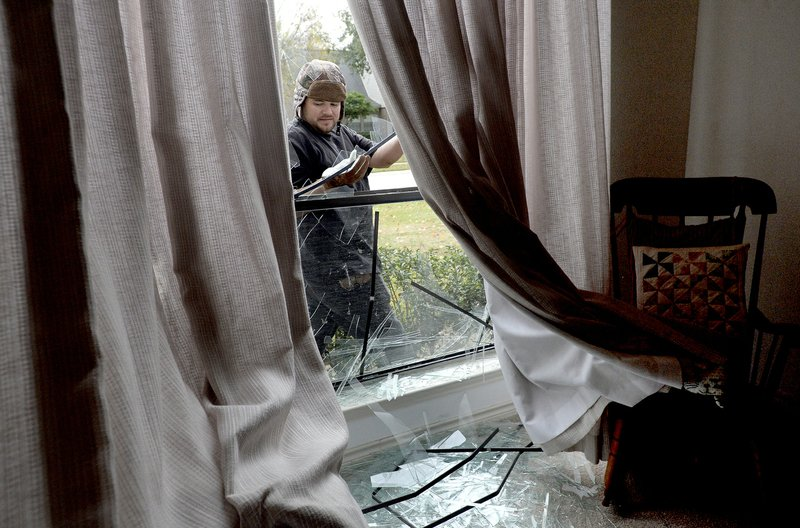Adrian Torres pulls shards of glass from a window frame following an explosion at the TPC plant Wednesday, Nov. 27, 2019, in Port Neches, Texas.  Three workers were injured early Wednesday in a massive explosion at the Texas chemical plant that also blew out the windows and doors of nearby homes.    (Kim Brent/The Beaumont Enterprise via AP)