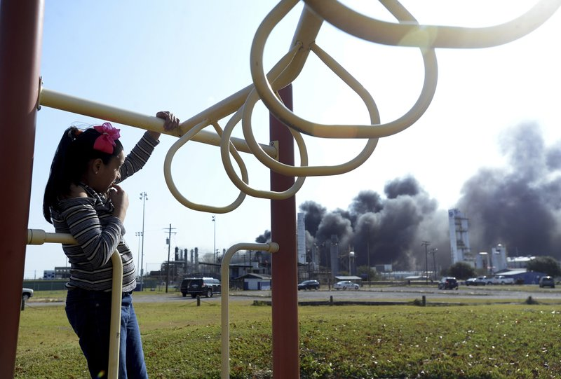 Adanli Puente watches the thick smoke and flames that continued to erupt from the TPC plant as she plays at a nearby park Wednesday, Nov. 27, 2019, in Port Neches, Texas.  Three workers were injured early Wednesday in a massive explosion at the Texas chemical plant that also blew out the windows and doors of nearby homes.    (Kim Brent/The Beaumont Enterprise via AP)