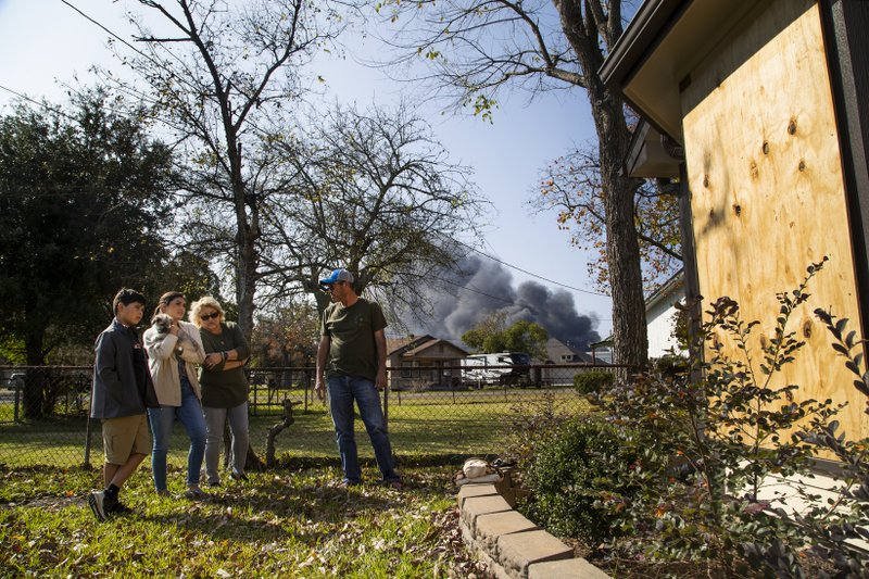 Milo Garcia, 10, Cecilia García, 19, and their grandparents Yolanda Rosales and Luis Rosales take a look at the windows covered in panels after they shattered during the TPC Group Port Neches Operations explosion on Wednesday, Nov. 27, 2019, in Port Neches., Texas.  Three workers were injured early Wednesday in a massive explosion at the Texas chemical plant that also blew out the windows and doors of nearby homes.  (Marie D. De Jesus /Houston Chronicle via AP)
