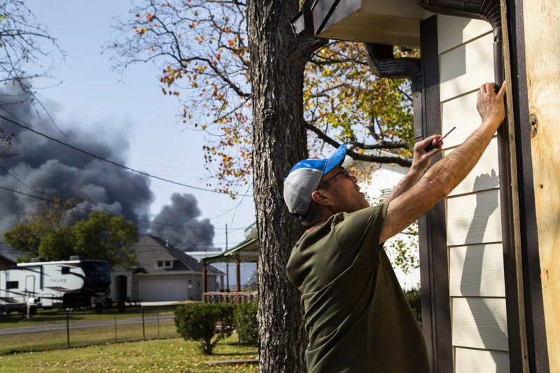 Luis Rosales repairs the drainage of his home on Wednesday, Nov. 27, 2019, in Port Neches after five windows shattered during the TPC Group Port Neches Operations explosion on Wednesday, Nov. 27, 2019, in Port Neches., Texas.  Three workers were injured early Wednesday in a massive explosion at the Texas chemical plant that also blew out the windows and doors of nearby homes.  (Marie D. De Jesus /Houston Chronicle via AP)