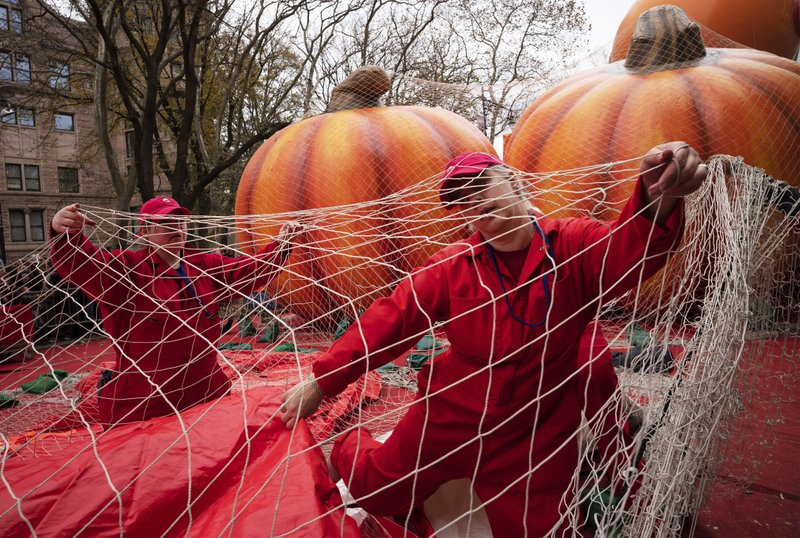 Michele Schleibaum, right, arranges protective netting on the Power Rangers Mighty Morphin Red Ranger balloon as it is inflated, Wednesday, Nov. 27, 2019 in New York. The netting will be in place overnight. New York City's big Macy's Thanksgiving Day Parade on Thursday will take place amid strong winds that could potentially ground the giant character balloons. (AP Photo/Mark Lennihan)