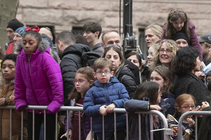 Crowds watch as the balloons for the Macy's Thanksgiving Day Parade are inflated, Wednesday, Nov. 27, 2019 in New York. The city's parade on Thursday will take place amid strong winds that could potentially ground the giant character balloons. (AP Photo/Mark Lennihan)
