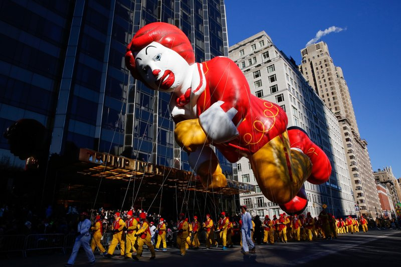 FILE - In this Nov. 22, 2018 file photo, the Ronald McDonald balloon passes by windows of a building on Central Park West during the 92nd annual Macy's Thanksgiving Day Parade in New York.  Macy's Thanksgiving Day Parade on Thursday, Nov. 28, 2019, will take place amid strong winds that could potentially ground the giant character balloons. The balloons have caused mishaps and injuries in the past when gusts blew them off course. (AP Photo/Eduardo Munoz Alvarez, File)