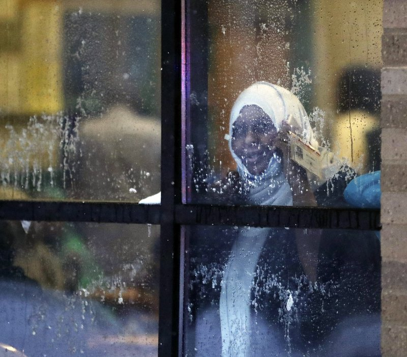 A displaced resident looks out a window after a deadly fire at a high-rise apartment building Wednesday, Nov. 27, 2019, in Minneapolis. (David Joles/Star Tribune via AP)