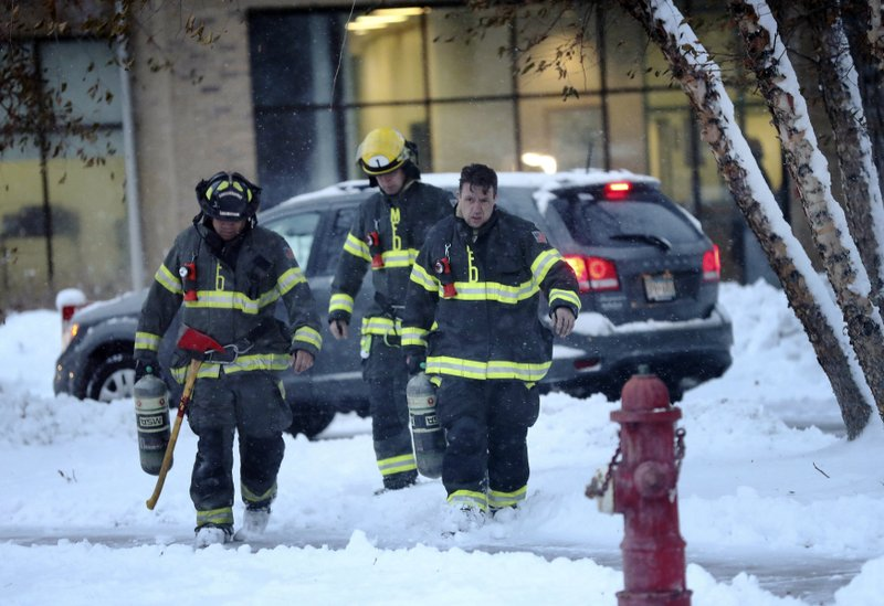 Minneapolis firefighters leave high-rise apartment building after a deadly fire Wednesday, Nov. 27, 2019, in Minneapolis. (David Joles/Star Tribune via AP)